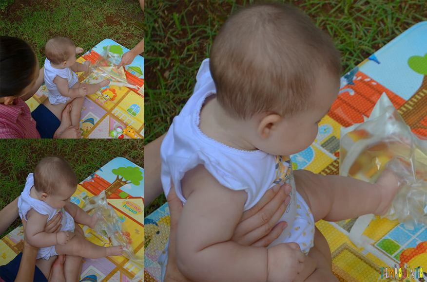 Brincadeira sensorial que ajuda o bebê a ficar de bruços - Luisa brincando com o plastico no pe