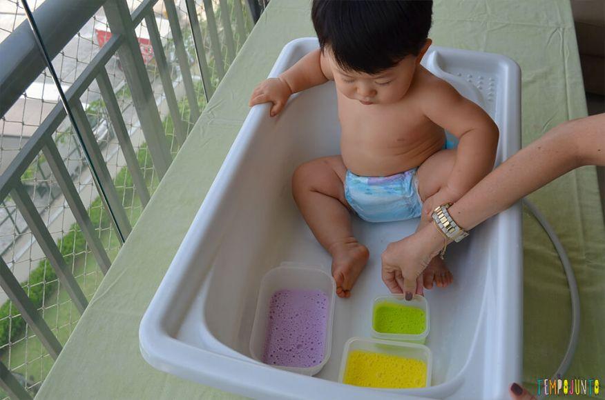 Brincadeira sensorial com espuma colorida para bebês - felipe olhando as espumas