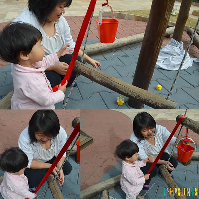 Despertar a curiosidade do bebê com uma brincadeira de causa e efeito - bebe brincando com a roldana