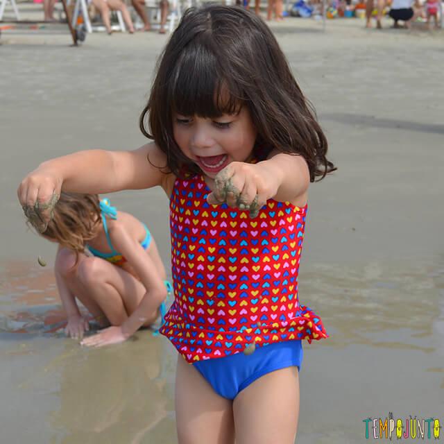 Dicas de estímulo sensorial e físico nas brincadeiras na praia - larissa com areia na mao