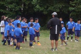 El profesor de educación física en plena tarea de enseñanza de fútbol a los niños.