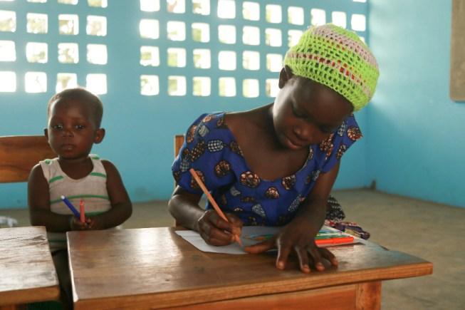 Una bambina disegna in un'aula in muratura