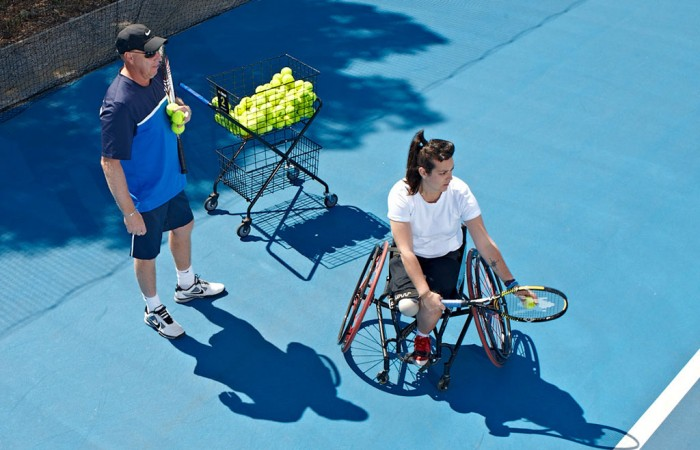 Coach and wheelchair tennis player practising serve.