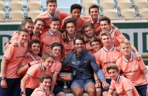 Rafael Nadal of Spain poses with the trophy and ball boys and girls after winning the men?s final match against Dominic Thiem of Austria during the French Open tennis tournament at Roland Garros in Paris, France, 09 June 2019. Nadal won the French Open title 12th times. EPA-EFE/SRDJAN SUKI