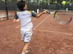 Junior tennis player hitting a forehand