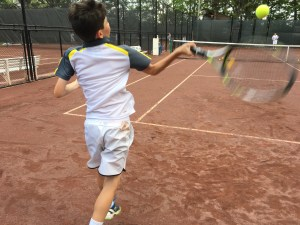 Junior tennis player hitting a forehand