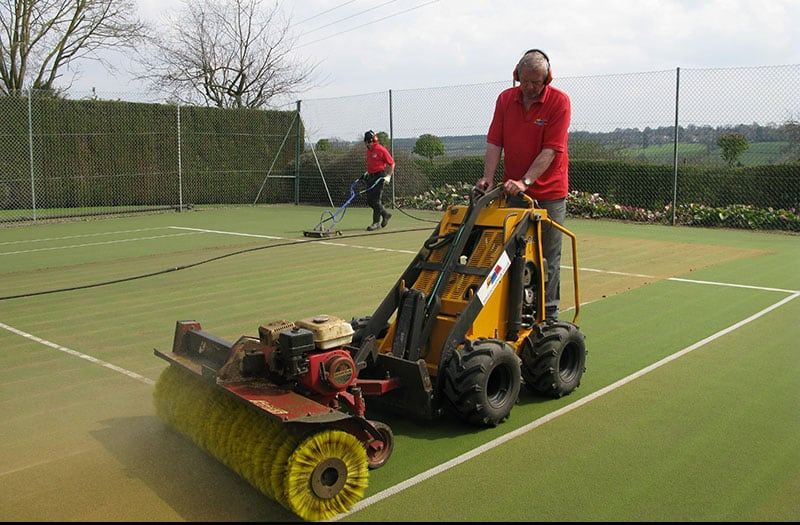 Brushing and cleaning a synthetic grass tennis court