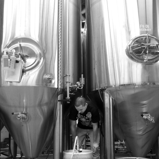 """Photo by Mario Bartel Jordan """"Chardonnay"""" Wong fills a cask amidst the towering 3,000 litre stainless steel tanks."""