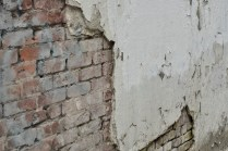 Photo © Kevin McConnellExposed brick underneath a layer of stucco on a wall on Front St.