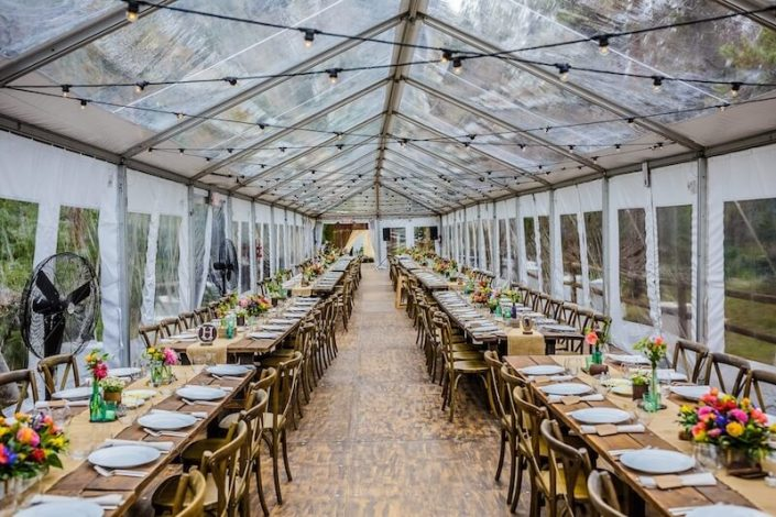 Clear Tent Rental With Bistro Lighting, Wooden Strata Flooring, Farm Tables & X Back Chairs