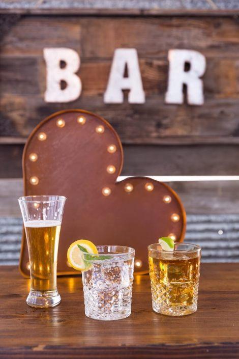 Beer Pilsner & Carat Rocks Glasses On Whiskey Barrel Bar With Barnwood Decor Wall & Bar Sign