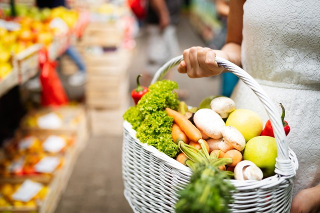 Woman holding a basket with healthy fresh organic vegetables
