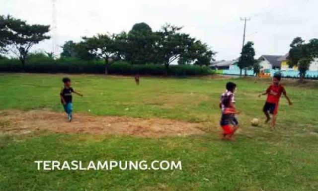 Anak - anak dan remaja asyik bermain bola di lapangan samping Koramil di Jalan Pahlawan, Kotabumi