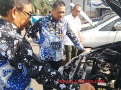 Penjabat Sekkab Lampung Utara, Sofyan sedang memeriksa mesin salah satu mobil dinas.