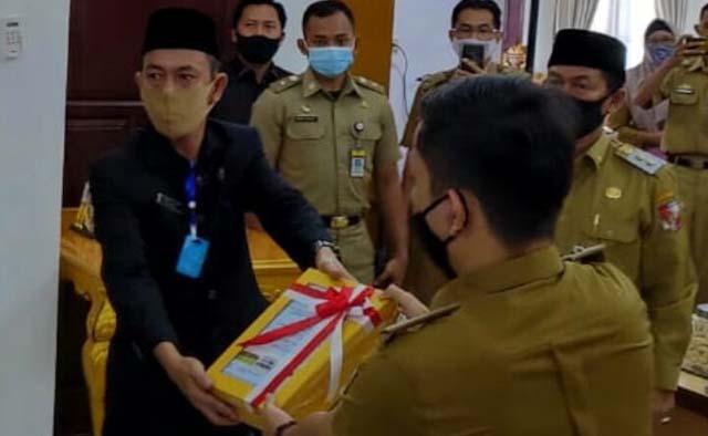 Ketua DPRD Lampung Utara, Romli (kiri) disaksikan Plt. Bupati Budi Utomo menerima opini BPK