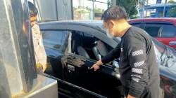 Anggota Polresta Bandarlampung menunjukkan lubang bekas peluru yang juga menembus pintu depan mobil sebelah kanan milik korban Kurnalis Asmarantaka. (foto;Ist)