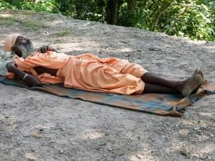 A wandering yogi sleeps by the roadside near Vashistha Gufa Cave, North of Rishikesh