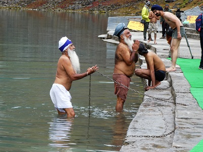 Sikh pilgrims paying homage at the lake edge - the chain is so they don't fall in