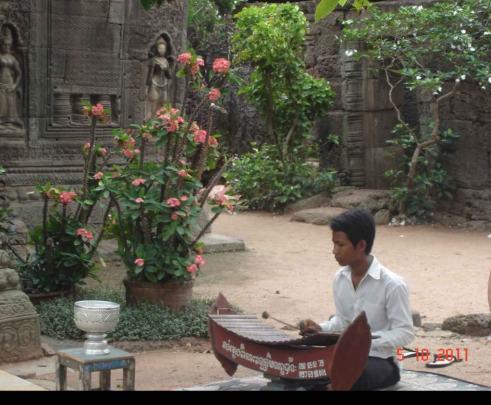 Young boy playing Cambodian Xylophone. Temple Ta Prohm, Takeo