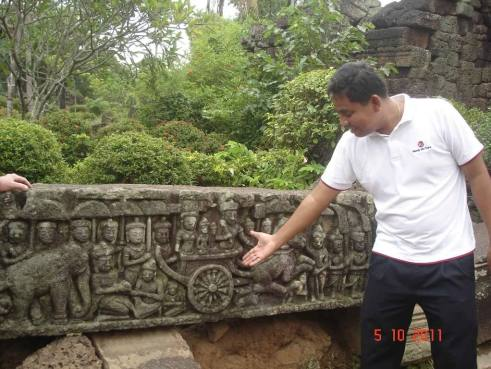 Guide explaining story on carved panel, Ta Prohm Temple, Takeo