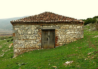 Stone hut on hill.