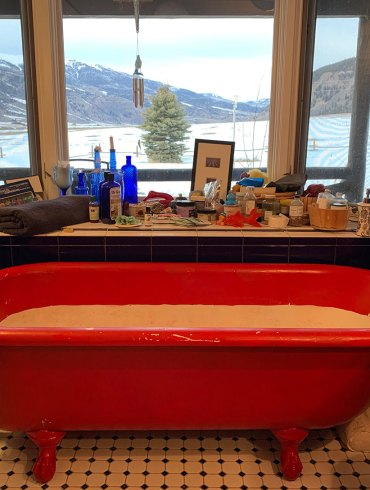 Bathtub with view of high country and mountains through windows