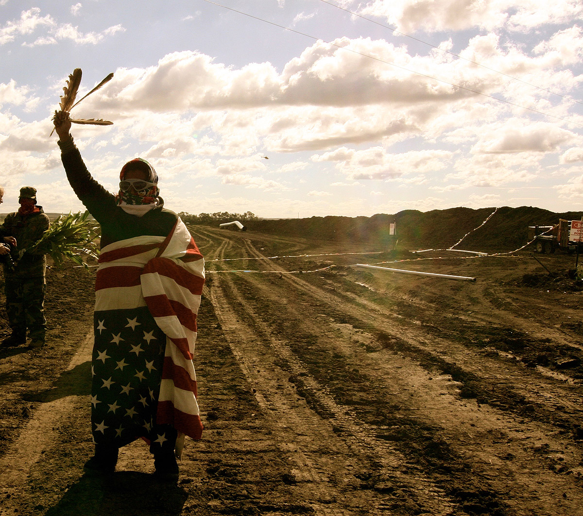 Native protestor wrapped in American flag and holding raptor feathers