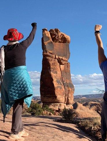 Women in desert raising fists
