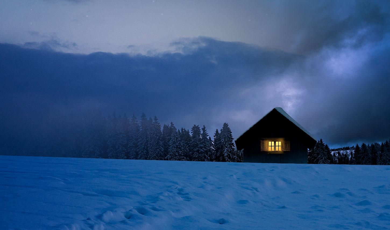 Snowy house with light window