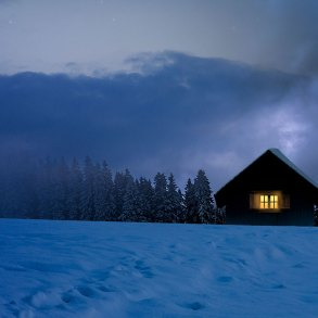 Snowy house with light window