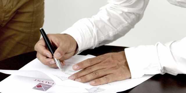 Una persona firma un documento