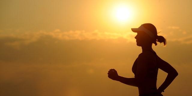 Mujer practicando running con el sol de fondo.