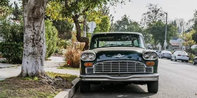 Chrysler clásico aparcado en una calle debajo de un árbol.