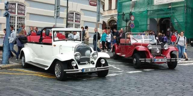 Dos coches clásicos expuestos en una calle concurrida.