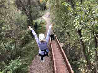 woman riding zip line with her arms raised.