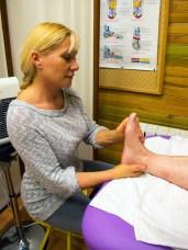 Catherine Bousquet en train d'effectuer un massage du pied sur un patient