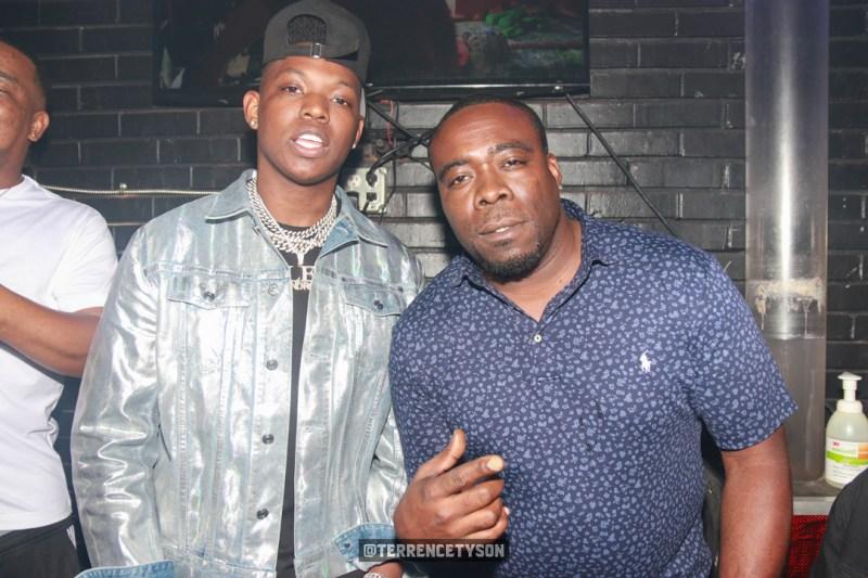 Rapper Yung Bleu wearing silver jacket ständig next to man in blue shirt