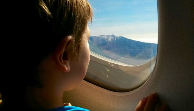 Julian vanuit het vliegtuig naar de Kilimanjaro kijkend