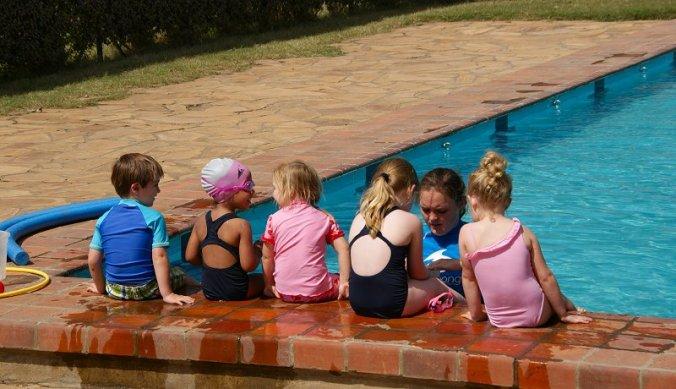 Zwemles aan rand van schoolzwembad