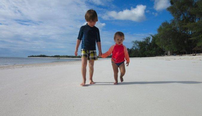 Broer en zus hand in hand op het strand van Zanzibar
