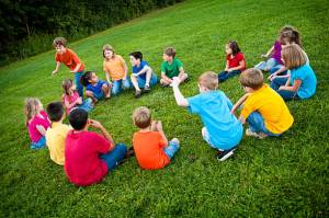 "Color photo of a group of boys and girls sitting in a circle and playing ""Duck, Duck, Goose!"" in the grass."