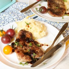 horizontal image of a simple pork tenderloin recipe with a parsley garnish plated on a white plate with some mashed potato and fresh cherry tomatoes