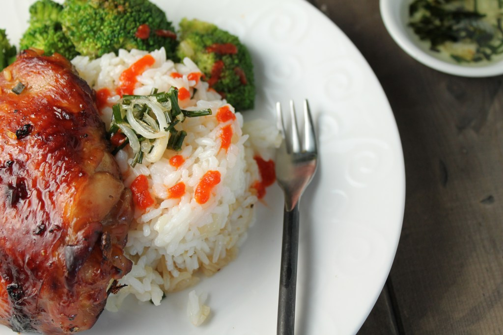 close up of an asian roasted chicken thigh atop a serving of white rice with a drizzle of scallion oil and steamed broccoli