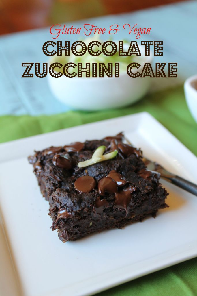 optimized for pinterest dark chocolate square of zucchini cake with melty chocolate chips and a a garnish of fresh zucchini on a white plate