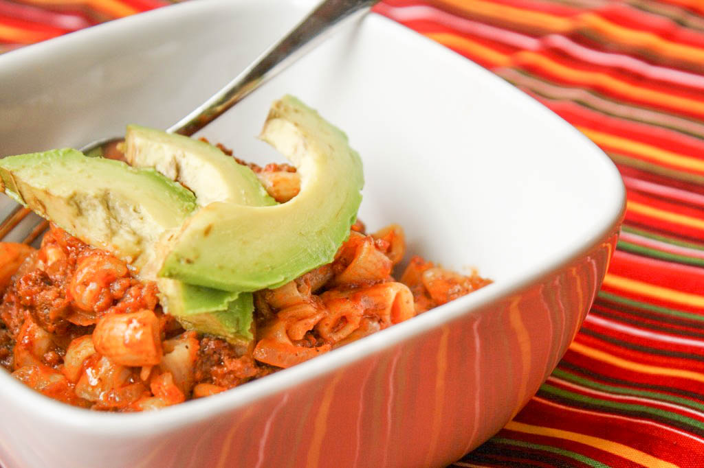 close up of gluten free chili mac noodles and hamburegr casserole on a festive striped cloth with a sliced avocado garnish