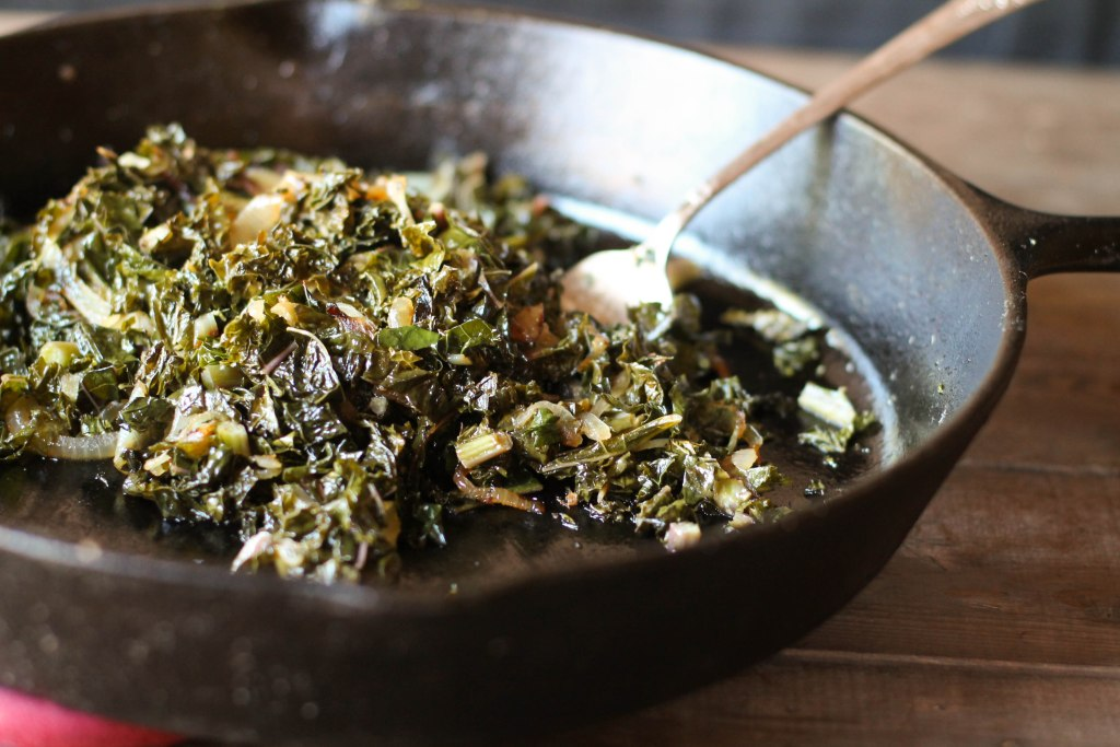 Sauteed Kale with Caramelized Onions in a cast iron pan looking from the side