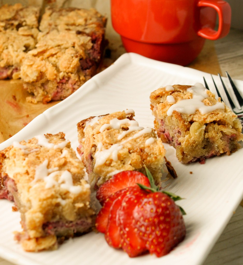 vertical image of 3 slices of strawberry almond coffee cake on a white plate with fresh cut berries