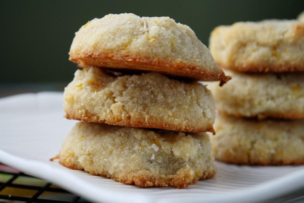 horizontal image of 3 stacked vegan orange almond cookies on white plate