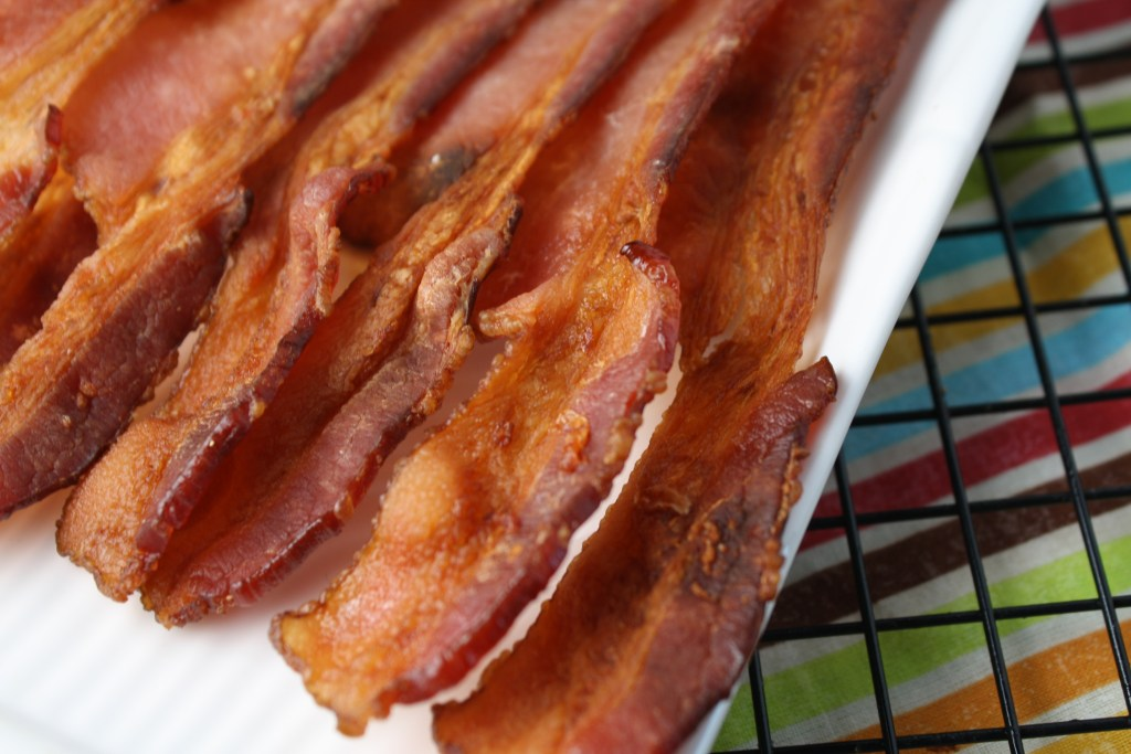 mess free crispy bacon close up on a white plate atop a rainbow striped cloth