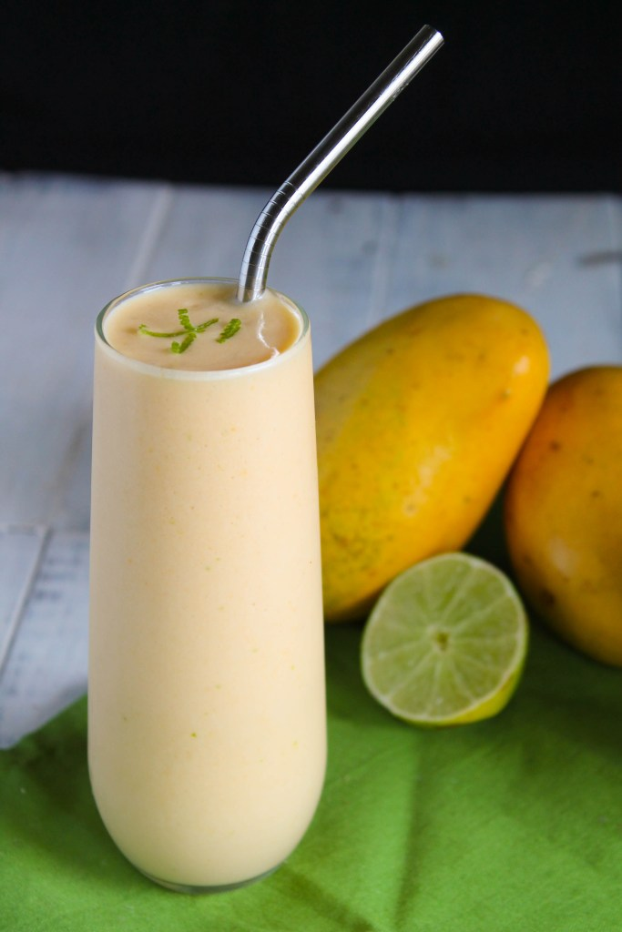 vertical image of a frosty cool orange hued smoothie in a clear glass with a stainless steel straw and garnish of fresh lime zest